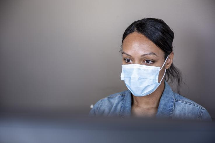 Woman wearing a mask sitting behind a computer monitor at the UW Belltown COVID-19 Clinic. Credit: University of Washington