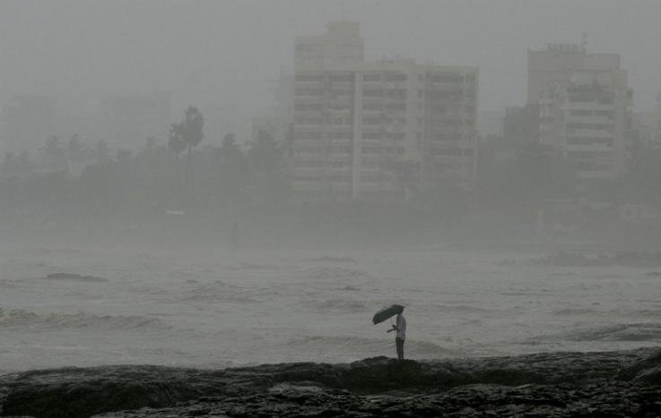 Photo of a man standing by the sea during heavy rain showers in Mumbai