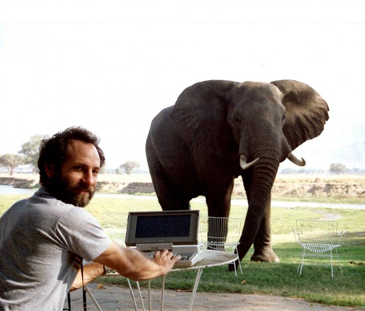Dr. Jay Kravitz in Lesotho seated at a table with a laptop in front of an elephant.
