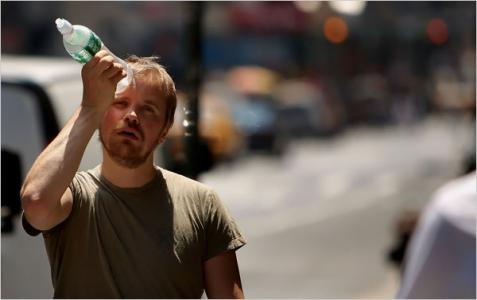 Photo of a man cooling himself off with a water bottle