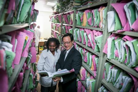 Photo of Dr. Michael Chung reviewing patient records with a colleague at Coptic Hope Center in Nairobi, Kenya