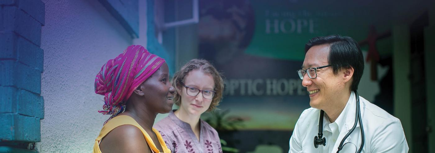 Photo of Dr. Michael Chung, Director of TREE, and Sharon Greene, a PhD student in Epidemiology, talking with a patient at the Coptic Hope Center in Nairobi, Kenya.