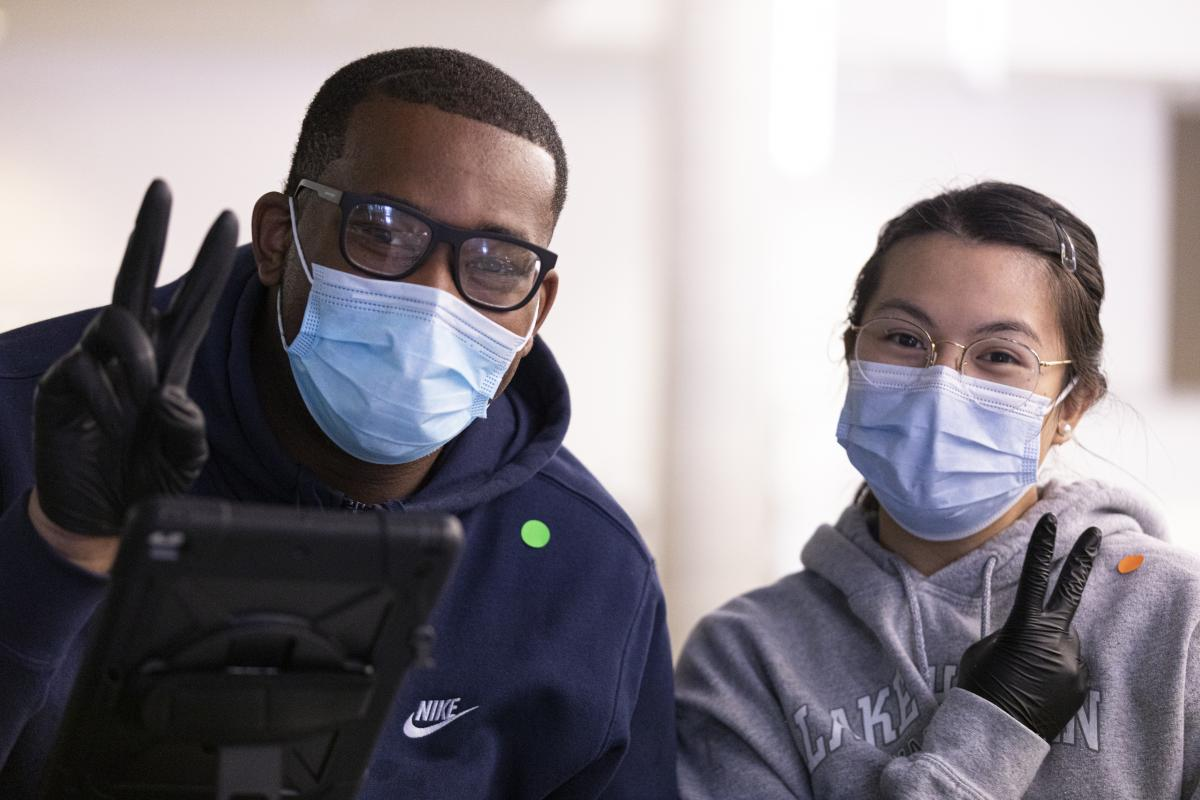 A man and woman side by side wearing disposable masks and black latex gloves, flashing the peace sign