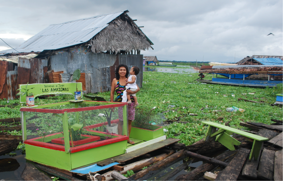 A mother holds her child in a community garden in Iquitos, Peru