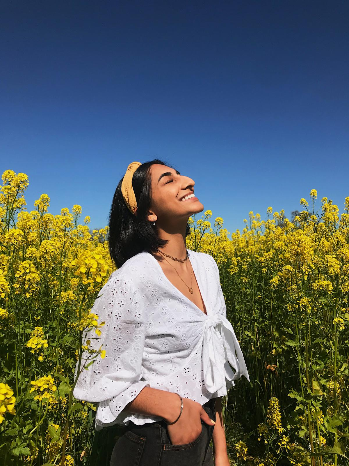 Portrait of Avneet Bhullar smiling in a field of flowers