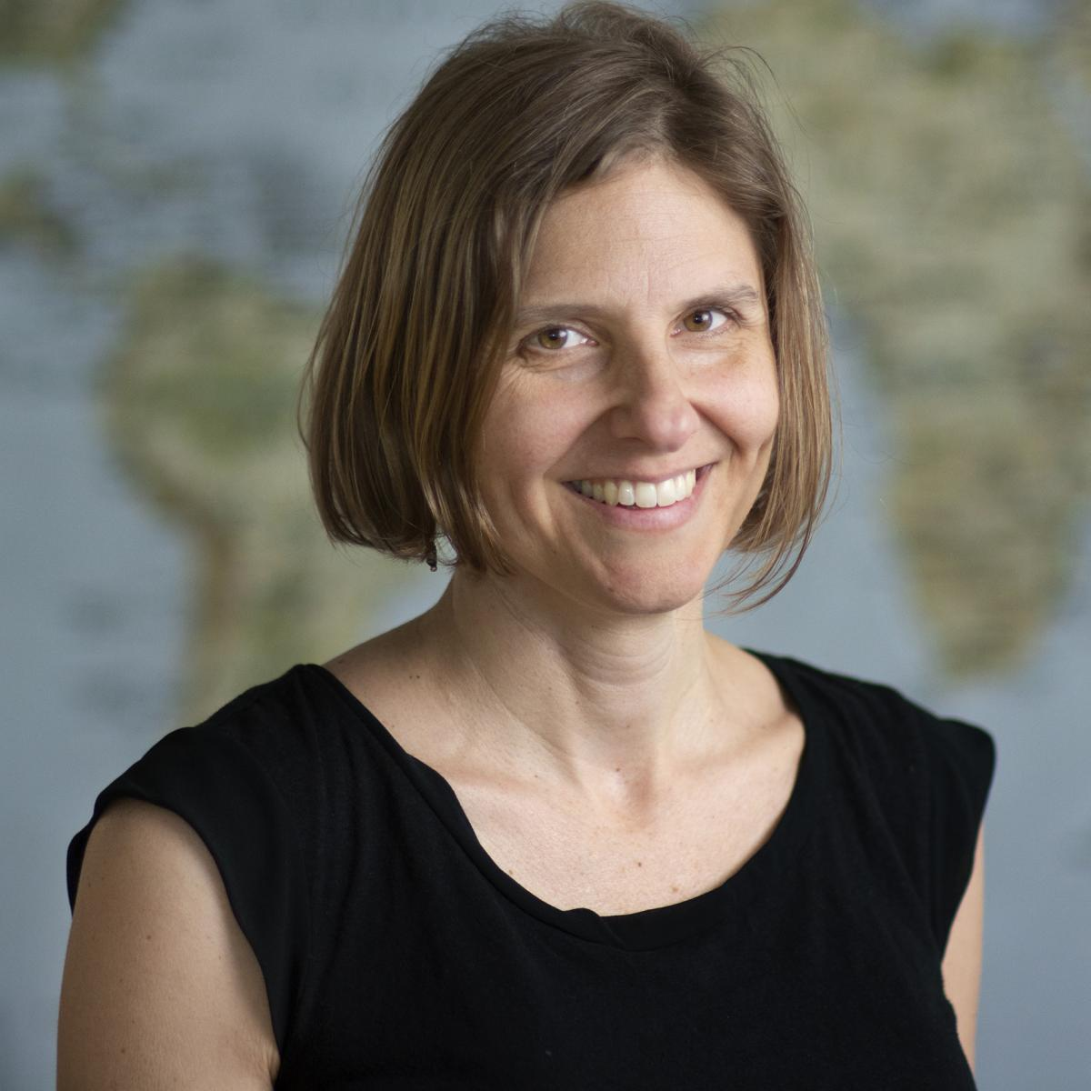 Profile photo of Anya Nartker in front of a world map