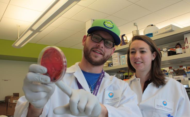 Photo of Jay and a fellow student looking at bacteria cultures