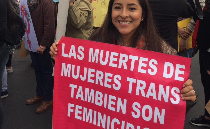 Photo of Katherine holding a sign that says The Deaths Of Trans Women Is Femicide